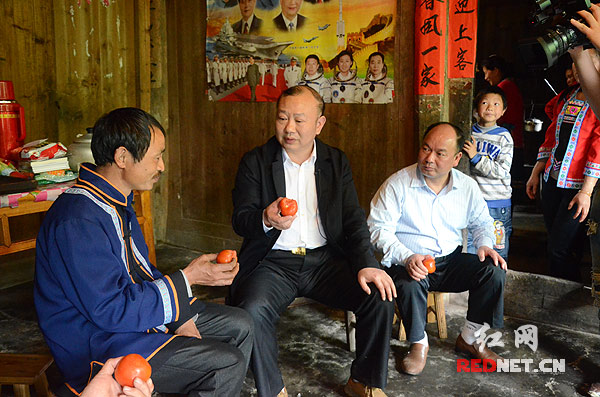 城步县长安营乡,村民阳孝和邀请罗建南尝尝自家种的西红柿。