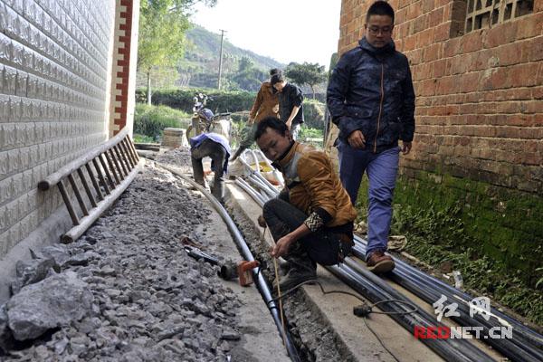 嘉禾县茂林村工人正在安装给水管道,目前全县273个行政村 (居委会)用上了自来水。