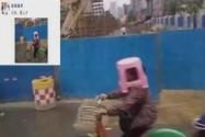 """[视频]大妈骑车未带雨具 板凳套头当""""雨伞"""""""